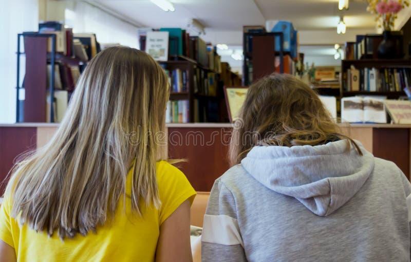 Twee meisjes die in de lezingsruimte zitten van de bibliotheek stock foto's