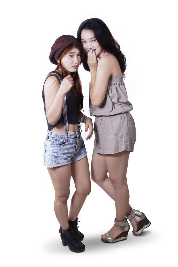 Twee meisjes die in de studio roddelen stock foto