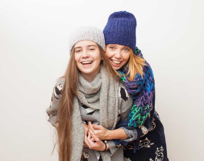 Twee meisjes die in de winterkleren op witte achtergrond lachen stock afbeeldingen