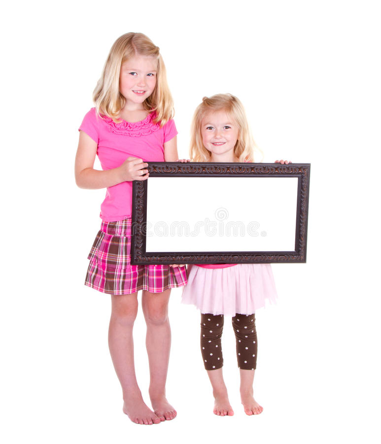 Twee meisjes die een leeg frame houden stock foto's