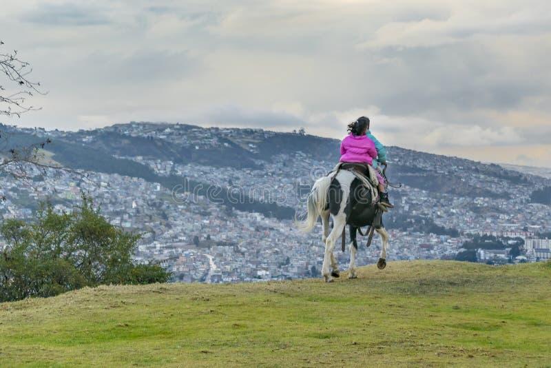 Twee Meisjes die een Paardquito Ecuador berijden royalty-vrije stock fotografie