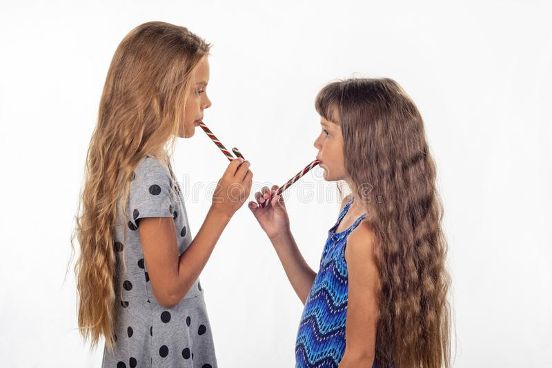 Twee meisjes die een riet gevormd suikergoed eten en die aan elkaar draaien stock afbeeldingen