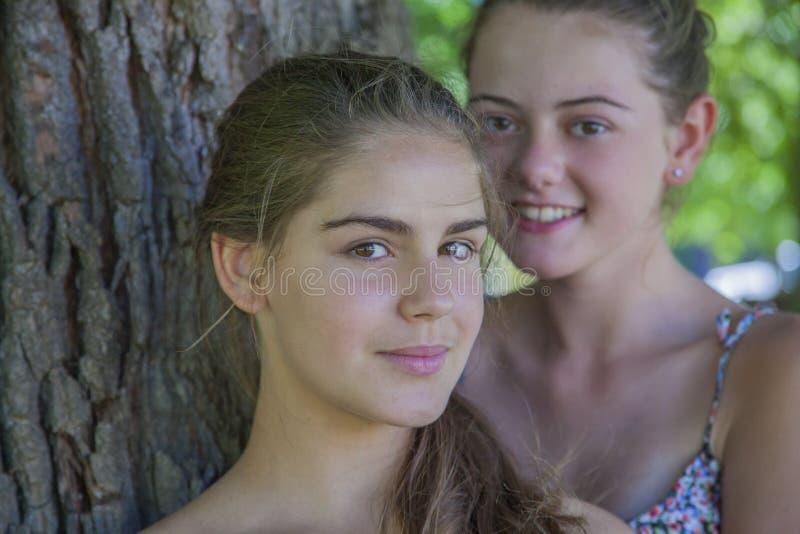 Twee meisjes die elkaar in bos koesteren stock fotografie