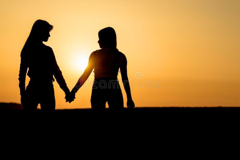 Twee meisjes die elkaar houden overhandigt De dames koppelen op het strand royalty-vrije stock afbeeldingen