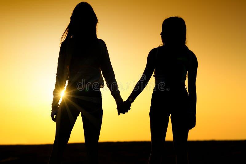 Twee meisjes die elkaar houden overhandigt De dames koppelen op het strand stock afbeelding