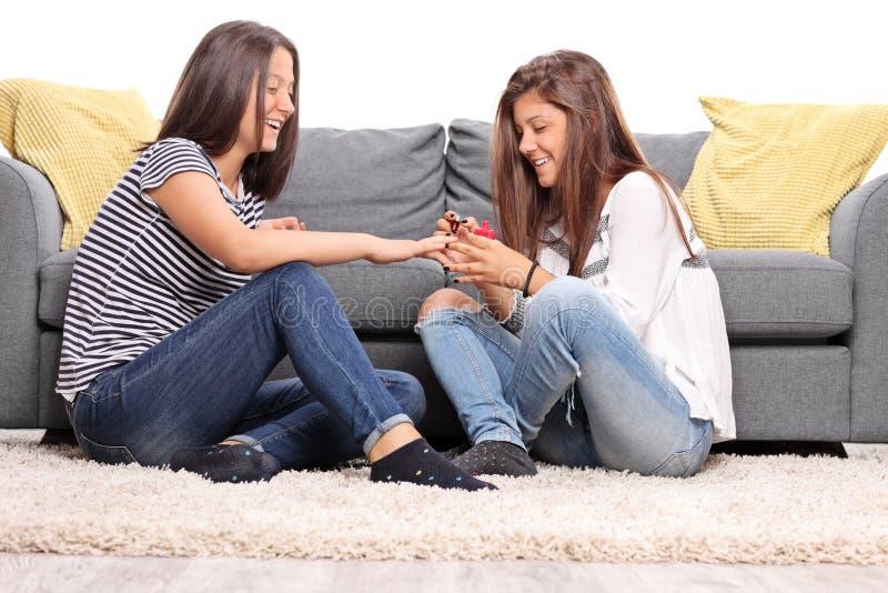 Twee meisjes die en hun spijkers zitten oppoetsen stock foto's