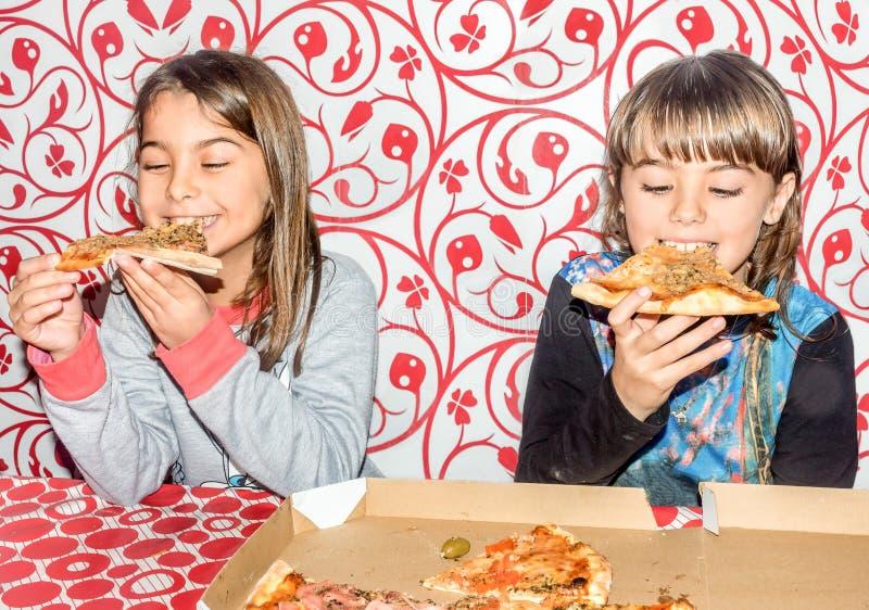 Twee meisjes die en pizza zitten eten stock afbeeldingen