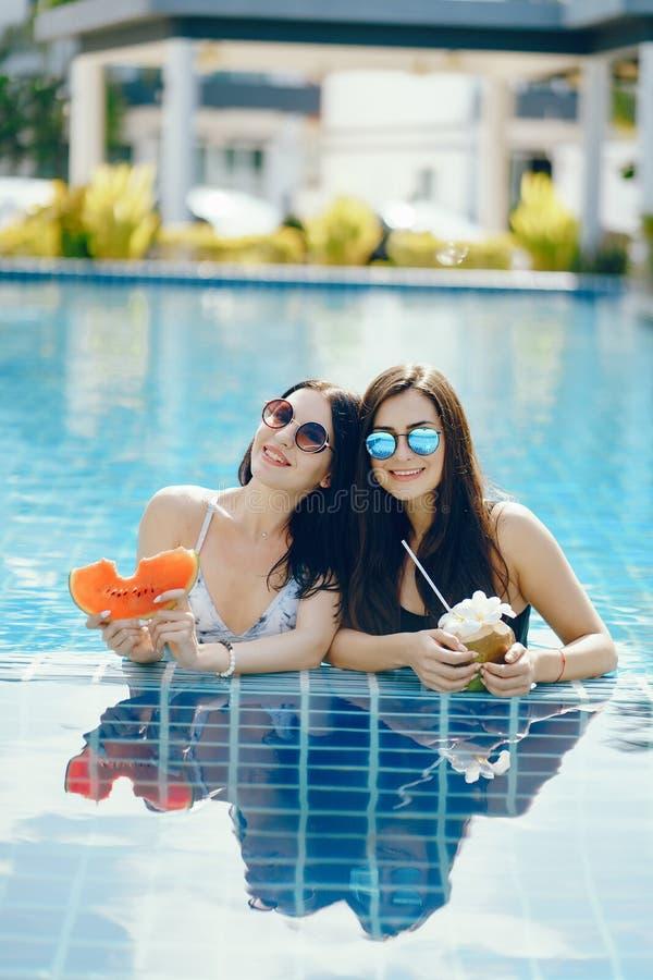 Twee meisjes die fruit hebben door de pool royalty-vrije stock foto