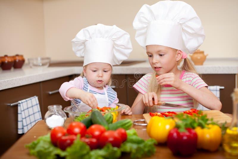 Twee meisjes die gezond voedsel op keuken voorbereiden royalty-vrije stock foto