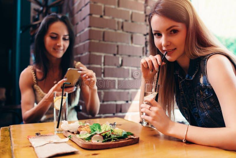 Twee meisjes die gezonde lunch in koffie hebben Jonge vrouw die beeld van voedsel met smartphone het posten op sociale media neme stock fotografie