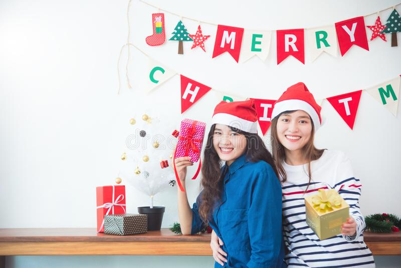 Twee meisjes die giftdozen en glimlach in Kerstmispartij thuis houden royalty-vrije stock foto