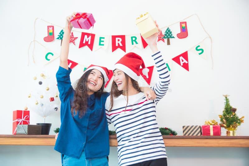 Twee meisjes die giftdozen en glimlach in Kerstmispartij thuis houden royalty-vrije stock afbeelding