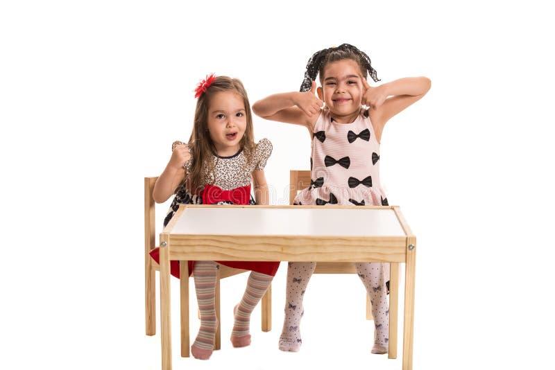 Twee meisjes die grappige gezichten en gebaren maken royalty-vrije stock foto's