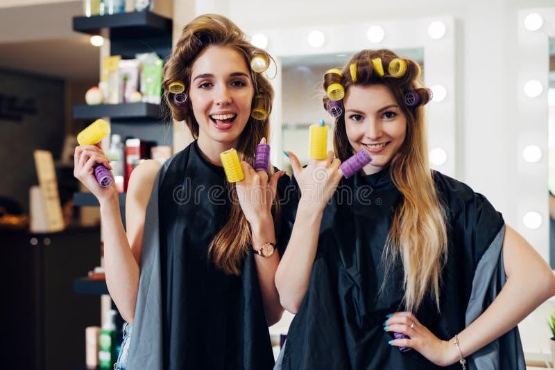 Twee meisjes die haar met krulspelden krullen die kaap dragen die pret hebben die zettend rollen op vingers in herenkapper lachen royalty-vrije stock afbeeldingen