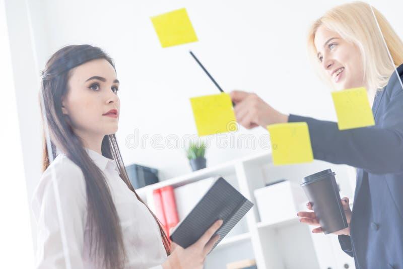 Twee meisjes die in het bureau spreken De meisjes zijn een dialoog dichtbij een transparante Raad met stickers stock fotografie