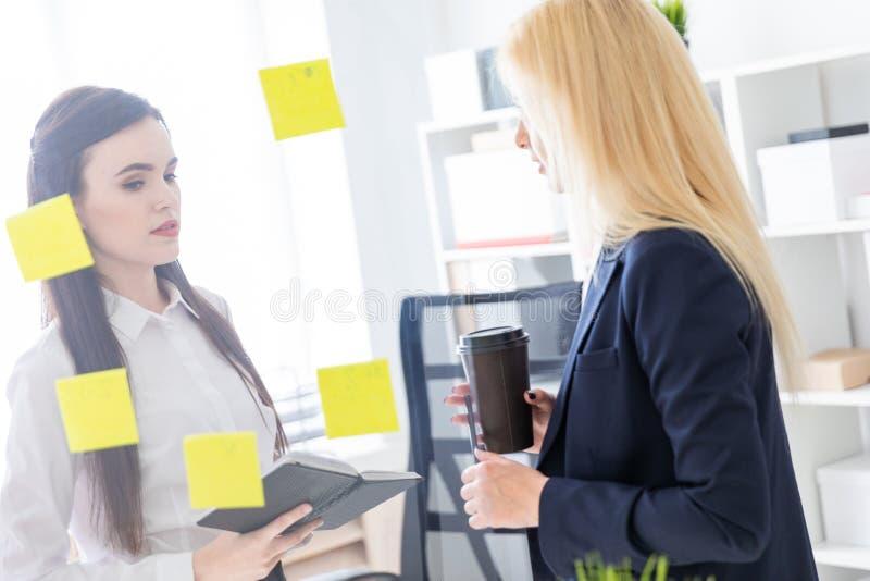 Twee meisjes die in het bureau spreken De meisjes zijn een dialoog dichtbij een transparante Raad met stickers stock foto's