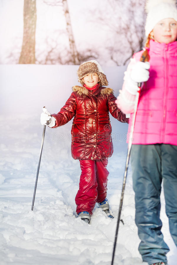 Twee meisjes die in het witte de winterbos ski?en stock fotografie