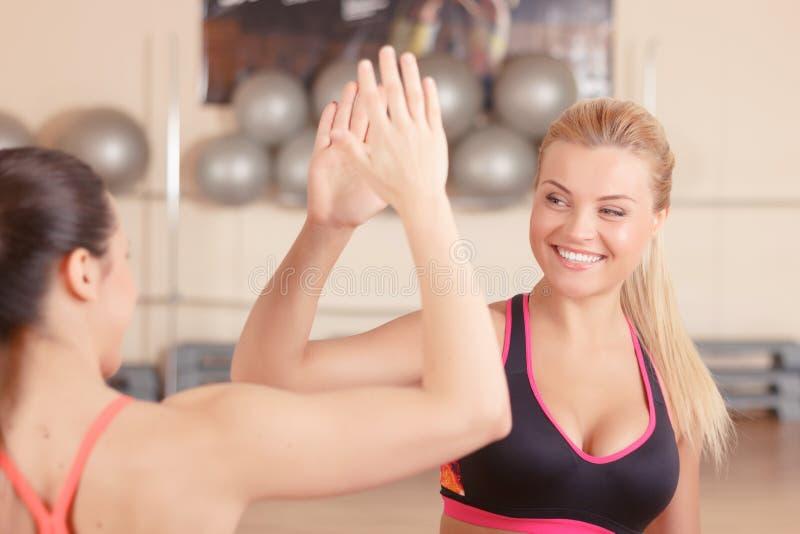 Twee meisjes die hoogte vijf in gymnastiek geven royalty-vrije stock afbeelding