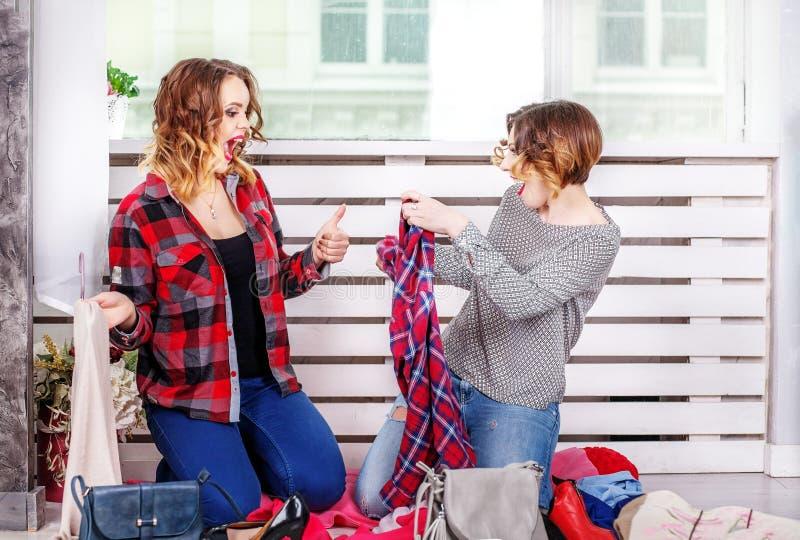 Twee meisjes die kleren van haar garderobe kiezen Het concept fashi royalty-vrije stock afbeeldingen