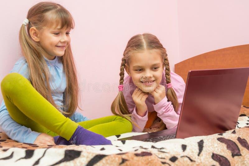 Twee meisjes die laptop bekijken stock fotografie