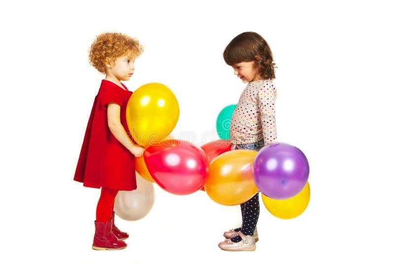 Twee meisjes die met ballons spelen stock afbeelding