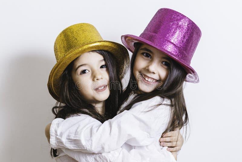 Twee meisjes die met gele en roze glanzende hoeden stellen stock foto