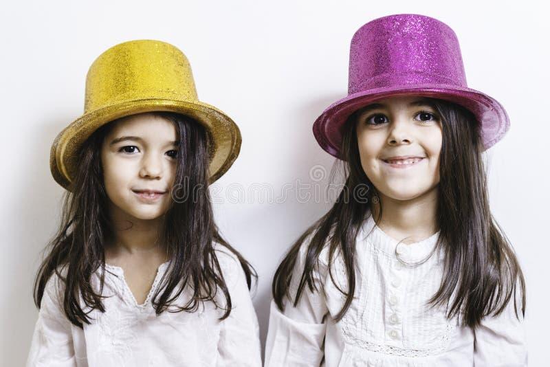 Twee meisjes die met gele en roze glanzende hoeden stellen stock afbeeldingen