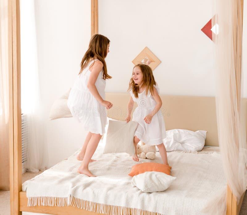 Twee meisjes die met hoofdkussens op het bed vechten stock foto
