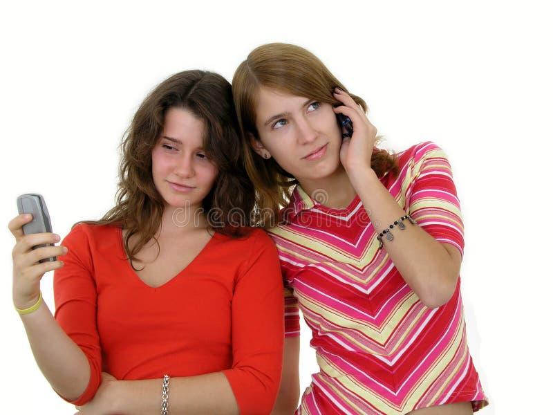 Twee meisjes die mobiele telefoons met behulp van stock afbeeldingen