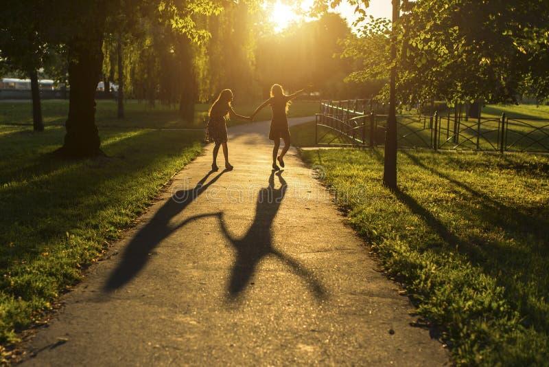 Twee meisjes die onderaan de handen van de steegholding, tijdens verbazende zonsondergang lopen stock fotografie
