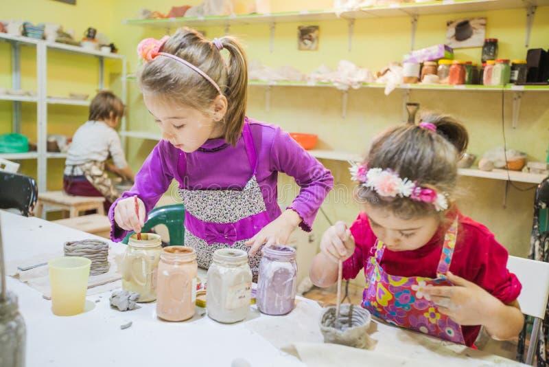 Twee Meisjes die op Aardewerkworkshop Clay Vase schilderen stock foto