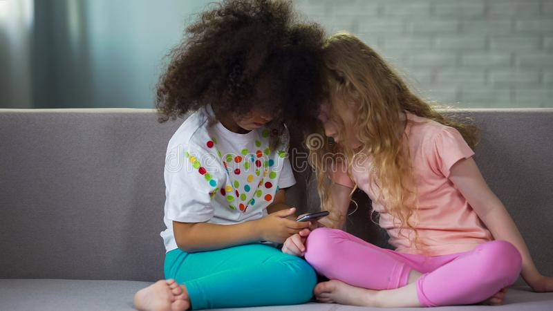 Twee meisjes die op bank zitten en op smartphone, moderne technologie spelen stock foto
