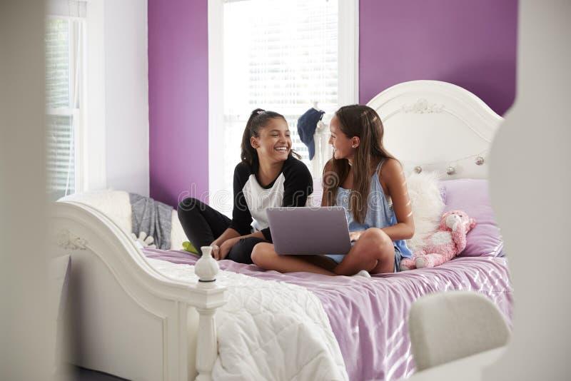 Twee meisjes die op bed met laptop zitten die elkaar bekijken stock afbeeldingen