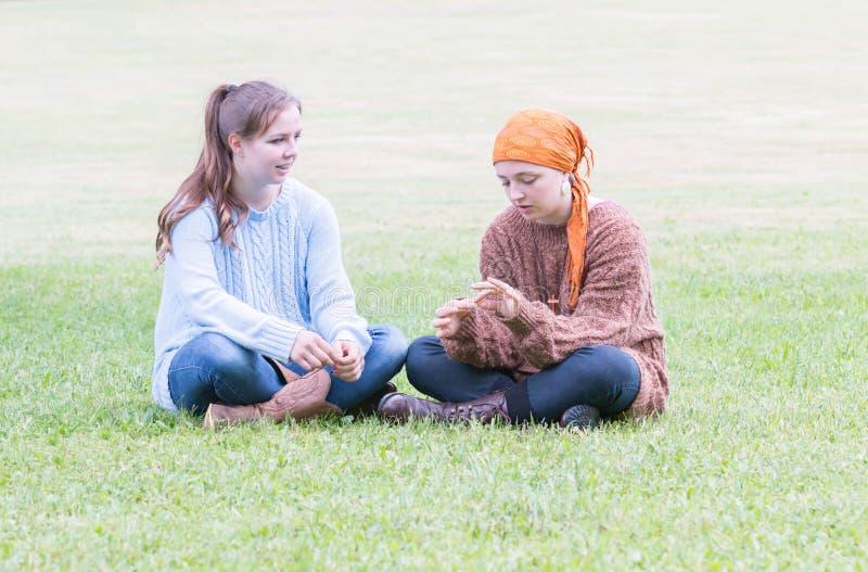 Twee meisjes die op gras zitten stock afbeeldingen