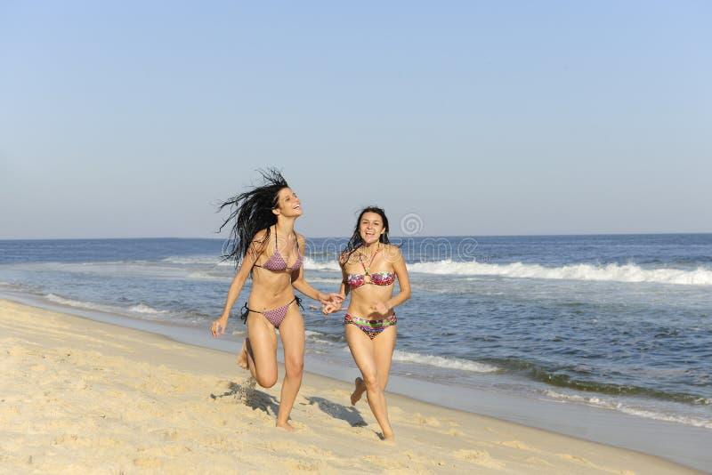 Twee meisjes die op het strand lopen stock afbeeldingen