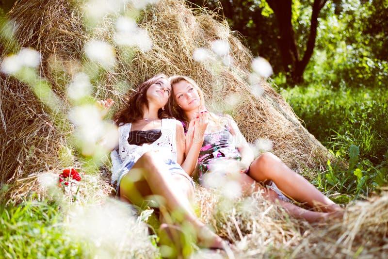 Twee meisjes die op hooi liggen stapelen royalty-vrije stock fotografie