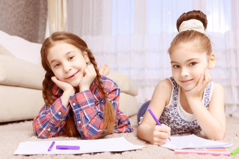 Twee meisjes die op tapijt liggen royalty-vrije stock afbeeldingen