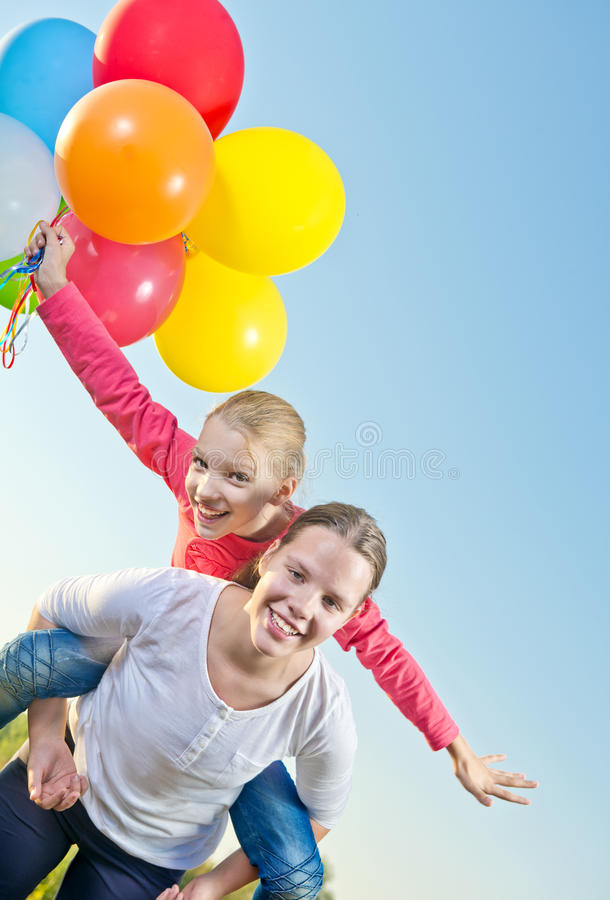Twee meisjes die in openlucht met ballons spelen royalty-vrije stock fotografie
