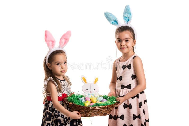 Twee meisjes die Pasen-mand houden stock fotografie