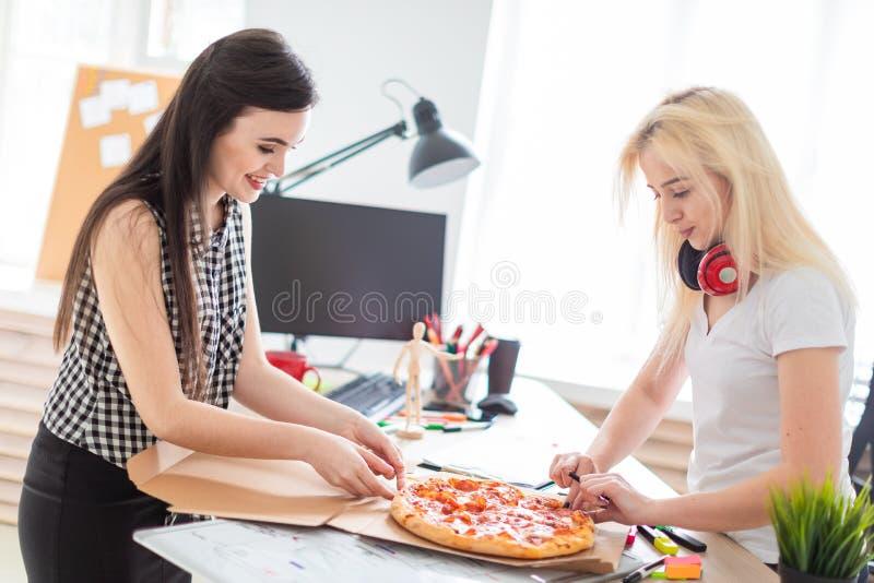 Twee meisjes die pizza in het bureau eten royalty-vrije stock foto