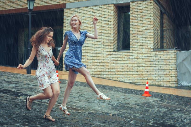 Twee meisjes die pret in de de zomerregen hebben royalty-vrije stock fotografie