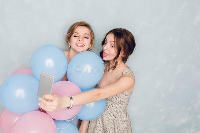 Twee meisjes die pret in een studio hebben en met blauwe en roze ballons spelen Het blonde meisje draagt blauwe kleding Donkerbru royalty-vrije stock fotografie