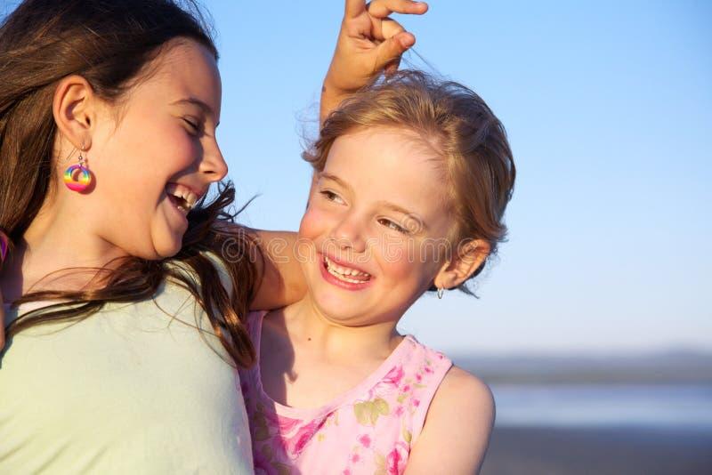 Twee meisjes die pret hebben bij strand stock fotografie