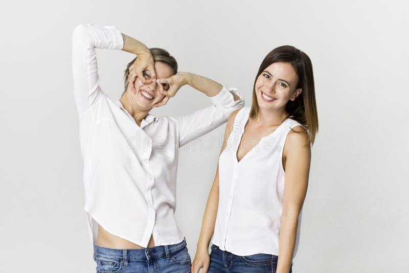 Twee meisjes die pret hebben bij studio Jong vrouw twee het glimlachen portret stock afbeeldingen