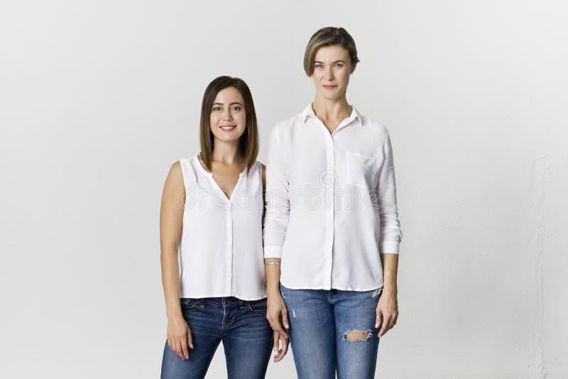 Twee meisjes die pret hebben bij studioachtergrond stock foto