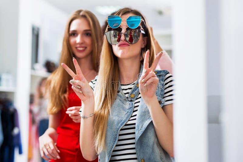 Twee meisjes die pret hebben terwijl het doen van het winkelen makend gezichten in de spiegel die v-Teken tonen die drie paar dra royalty-vrije stock foto's