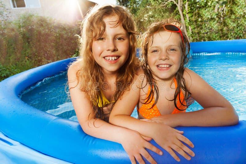 Twee meisjes die pret in zwembad hebben bij zonnige dag royalty-vrije stock afbeelding