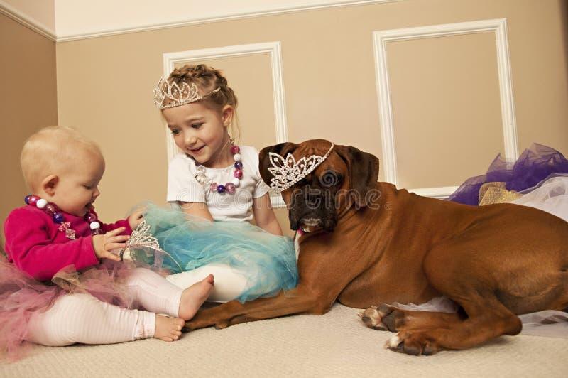 Twee meisjes die prinseskleding omhoog met een hond spelen royalty-vrije stock foto's