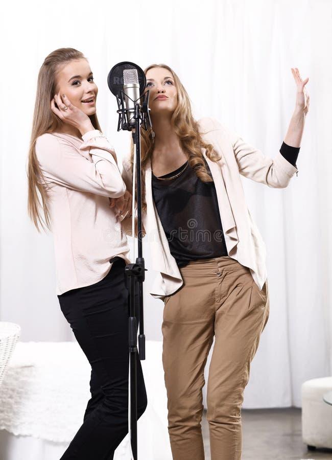 Twee meisjes die rond de microfoon in zingen stock foto