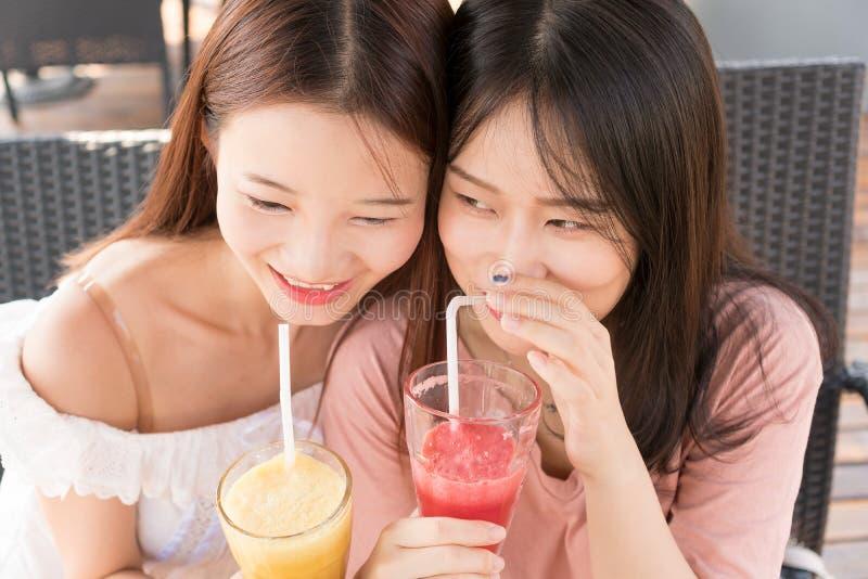 Twee meisjes die sap drinken stock afbeeldingen